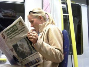 girl reading paper on subway